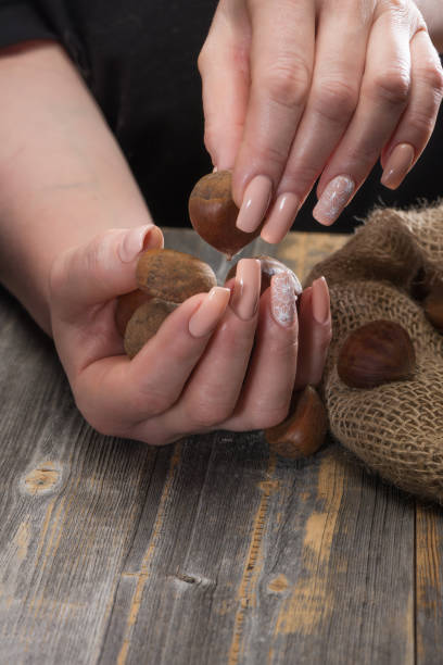 Cтоковое фото Female hands with beautiful magnificent manicure shift chestnuts from a linen bag on wooden boards