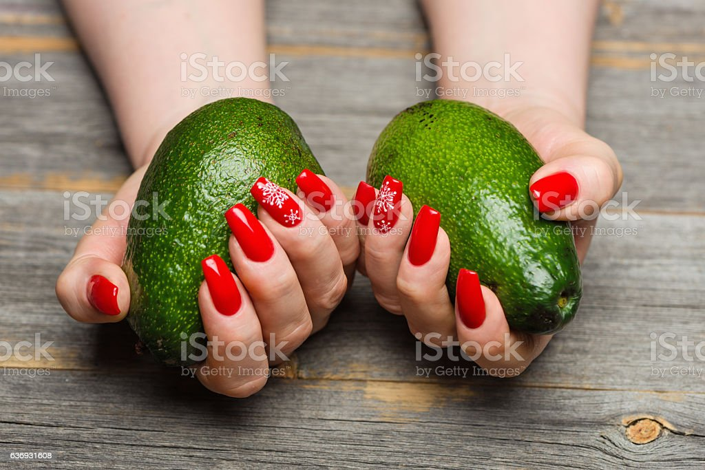 Female hands with beautiful New Year's manicure keep avocado стоковое фото