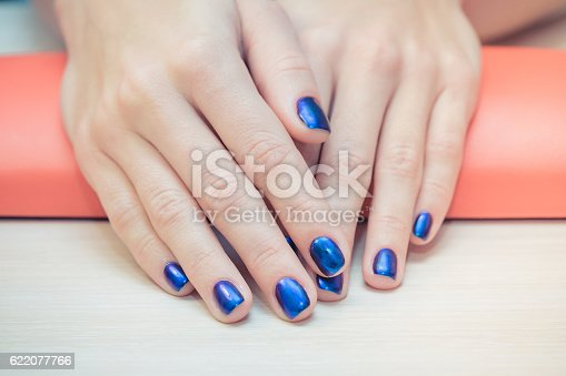 istock female hands with  blue nail Polish, close-up 622077766
