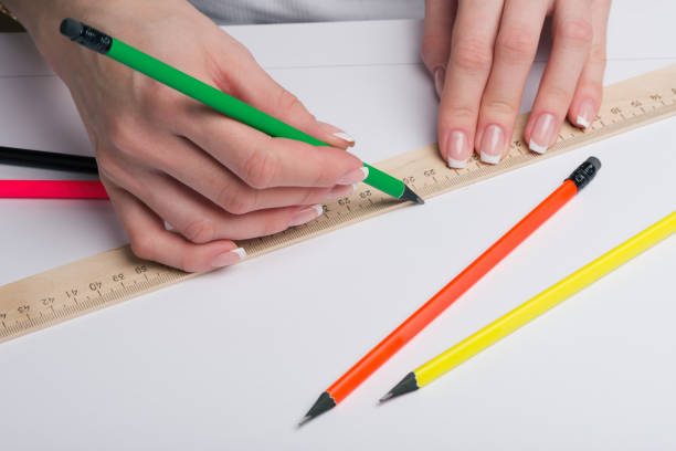 Cтоковое фото Female hands with classical French manicure draw a pencil by means of a ruler on clean standard sheet