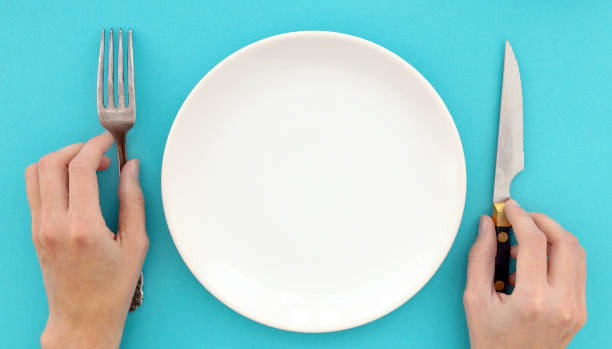 Female hands with cutlery and empty plate stock photo
