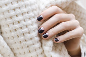 Female hands with dark brown nail design