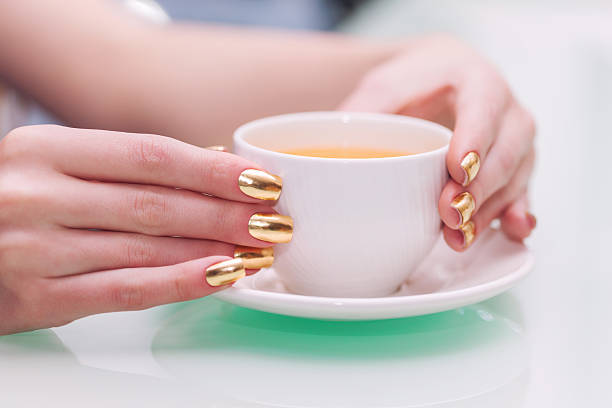 Female hands with elegant gold manicure hold cup of tea stock photo
