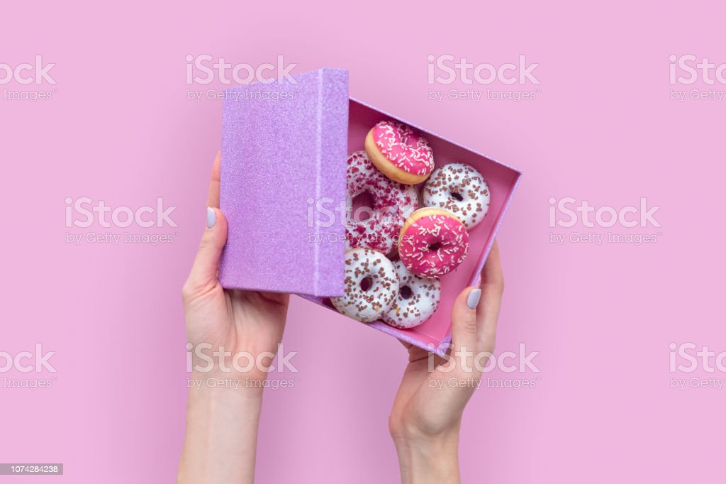 Female hands with open box with donuts on pink background.
