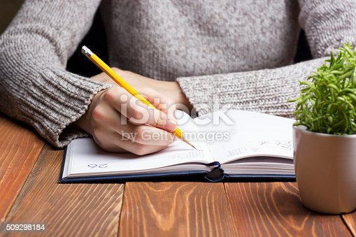 1147767708 istock photo female hands with pencil writing on notebook 509298184