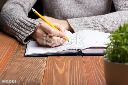 1147767708 istock photo female hands with pencil writing on notebook 515223938