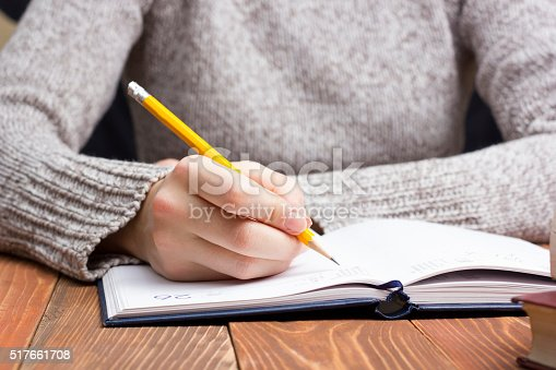 1147767708 istock photo female hands with pencil writing on notebook 517661708