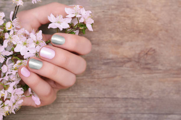 Female hands with pink and silver nail design stock photo