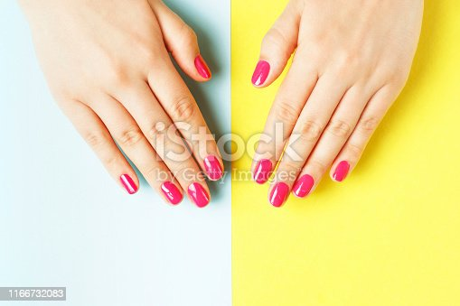 1128559926 istock photo Female hands with pink manicure on yellow and blue background 1166732083