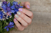 ピンクの爪のデザインで女性の手
