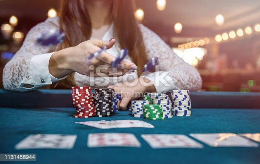 Female hands with playing cards and poker chips