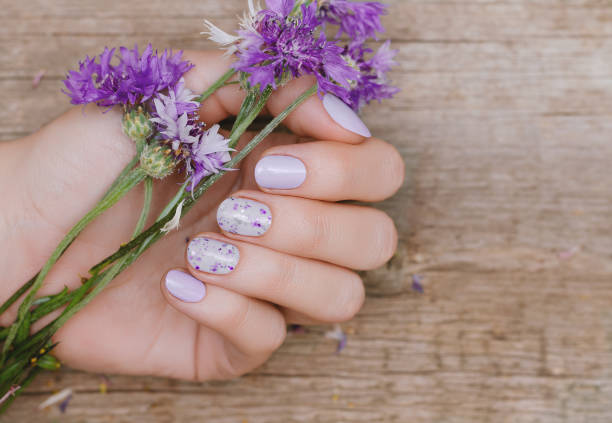Female hands with purple nail design stock photo
