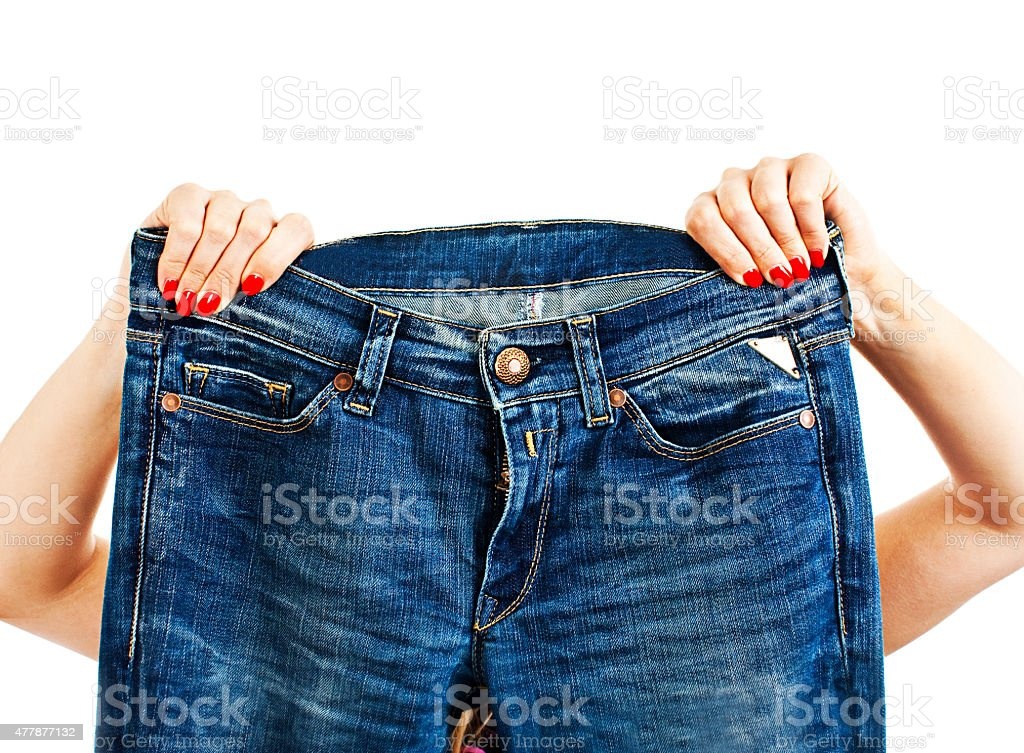 Female hands with red manicure holding blue jeans stock photo