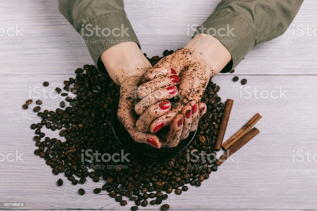 Female hands with red manicure with applied scrub stock photo