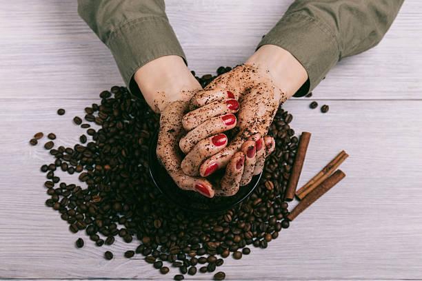female hands with red manicure with applied scrub - kaffeepeeling stock-fotos und bilder