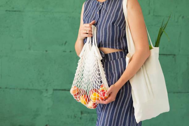 female hands with shopping cotton mesh eco bag on green background. zero waste concept - rifiuti zero foto e immagini stock