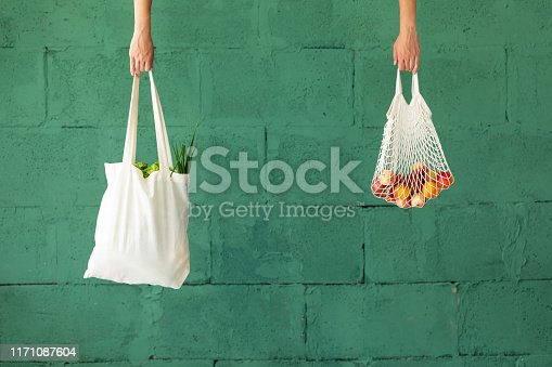 Female hands with shopping cotton mesh eco bag on green background. Zero waste concept
