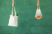 istock Female hands with shopping cotton mesh eco bag on green background. Zero waste concept 1171087604