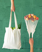 istock Female hands with shopping cotton mesh eco bag on green background. Zero waste concept 1171087618
