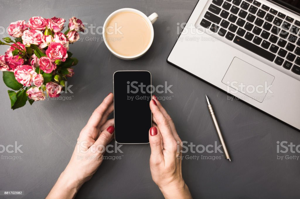 Female hands with smartphone, flowers, cup of coffee and laptop on gray table. Top view.