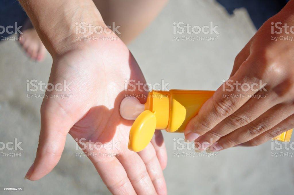 Manos femeninas con crema de protección solar. Concepto de cuidado de la piel. - foto de stock