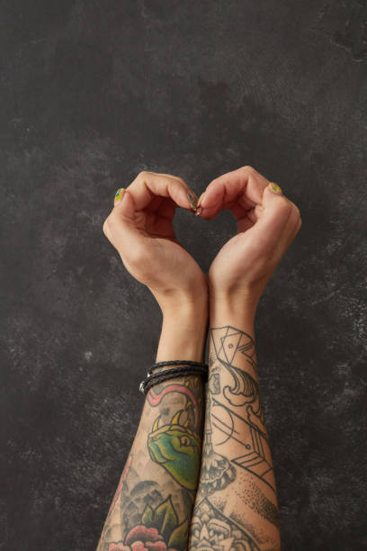 weibliche hände mit tattoos in form von herzen - lausbub tattoo stock-fotos und bilder
