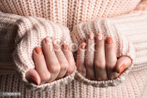 istock Female hands with trendy autumn marble manicure in orange color. 1276382876