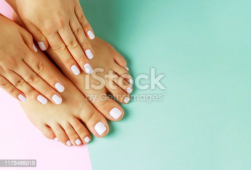 istock Female hands with white manicure and pedicure on pink and blue background, top view 1173495015