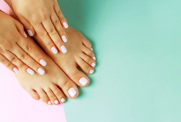 Female hands with white manicure and pedicure on pink and blue background, top view stock photo