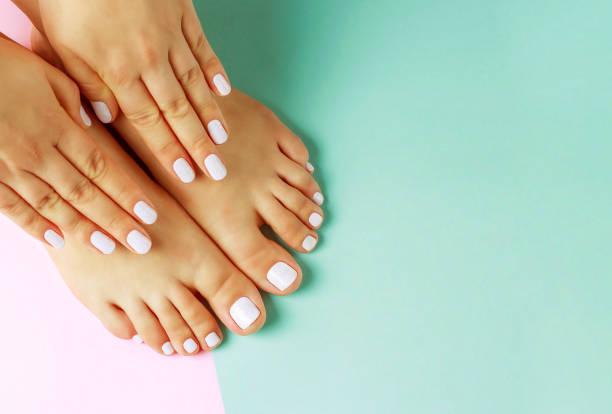 mãos fêmeas com manicure e o pedicure brancos no fundo cor-de-rosa e azul, vista superior - manicure - fotografias e filmes do acervo