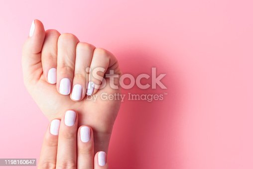 istock Female hands with white manicure on pink background with copy space 1198160647