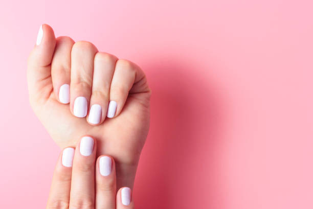 Female hands with white manicure on pink background with copy space stock photo