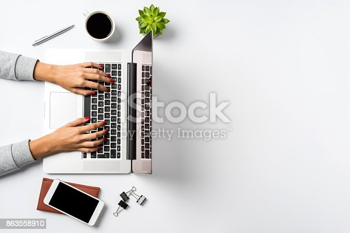 istock Female hands working on modern laptop. Office desktop on white background 863558910