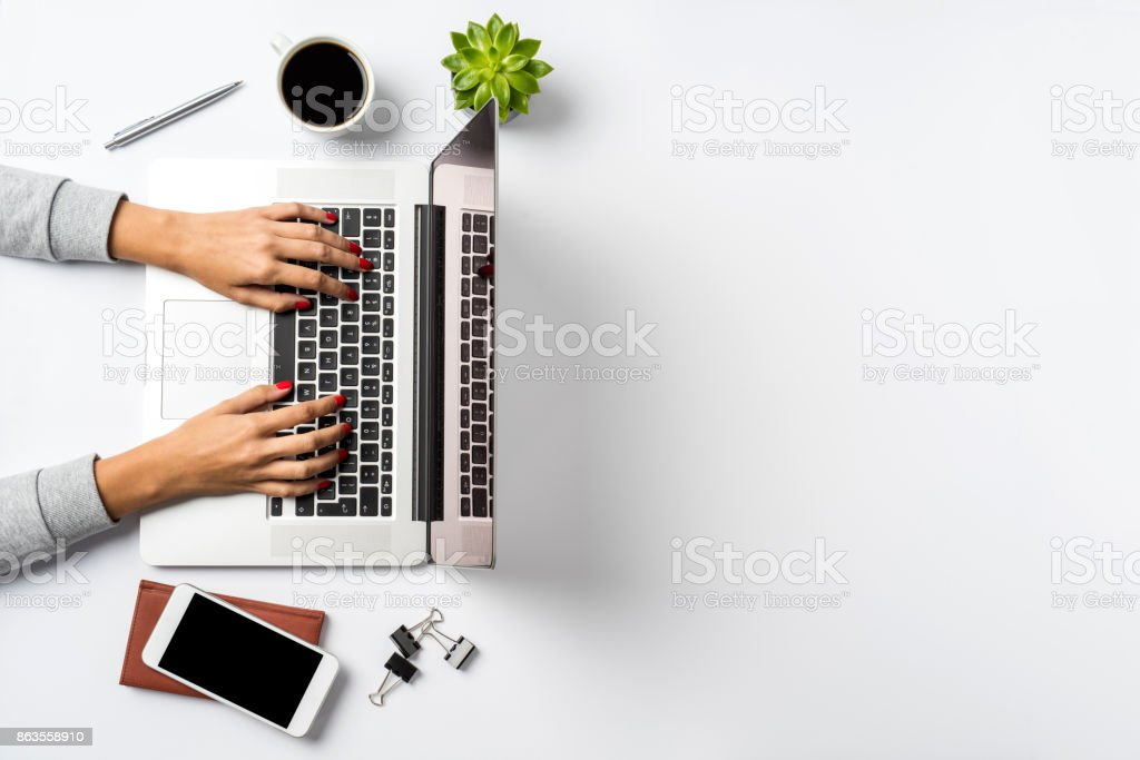 Female hands working on modern laptop. Office desktop on white background stock photo