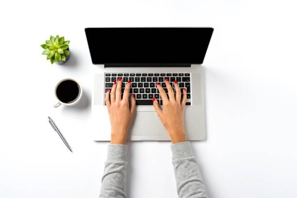 Female hands working on modern laptop. Office desktop on white background stock photo