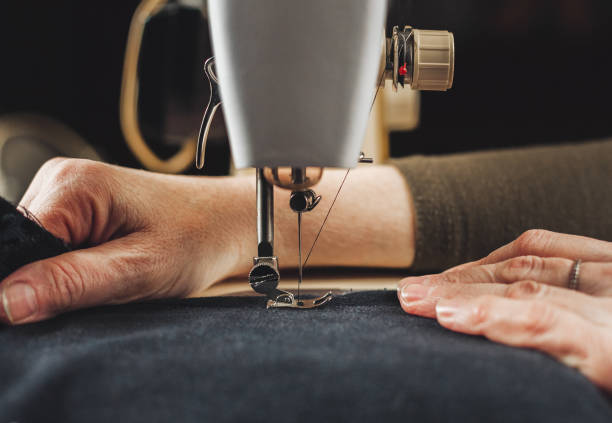 female hands working with sewing machine - sewing machine needle stock photos and pictures