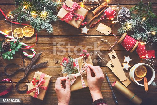 istock Female hands wrapping christmas holiday handmade presents 858960338