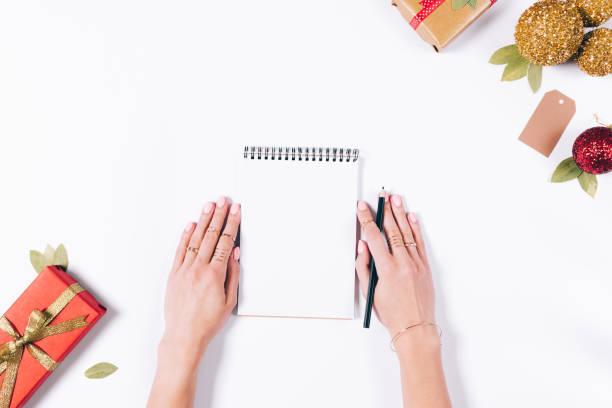 weibliche hände schreiben in ein notizbuch - bastelkarton stock-fotos und bilder
