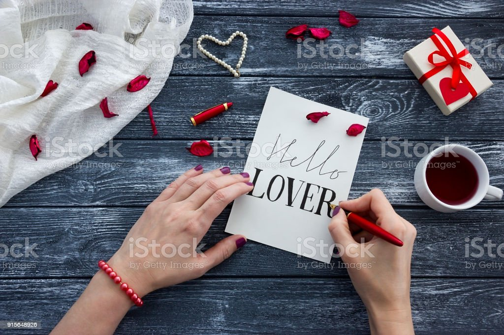 Female hands writing Red Pen a letter paper for Valentine\'s day with...