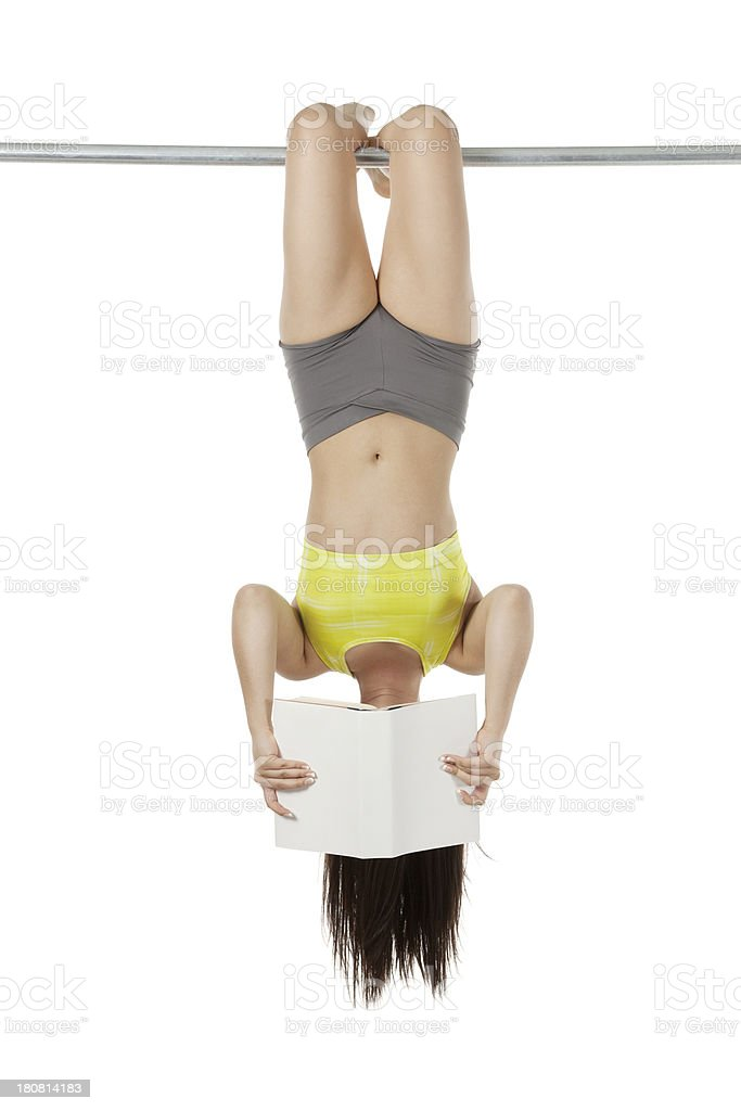 Female hanging upside down and reading book royalty-free stock photo