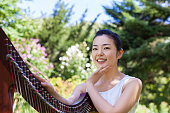 A Japanese female harpist is sitting next to her harp and smiling for the camera.