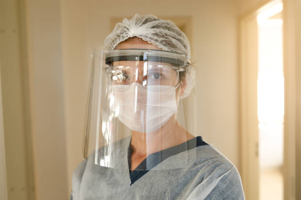 Female health care worker using face shield stock photo