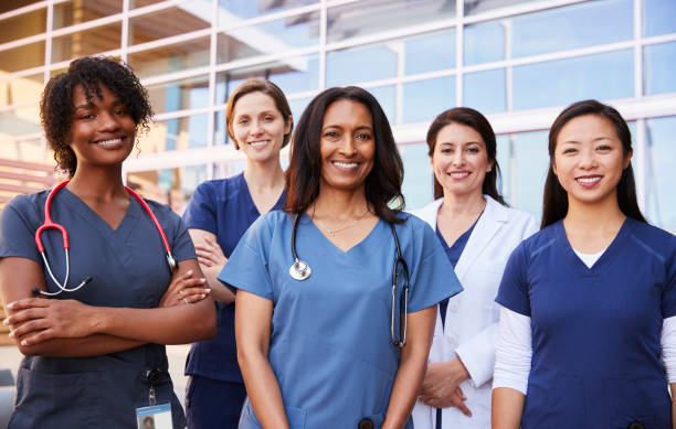 Female healthcare colleagues standing outside hospital stock photo