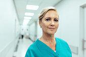 病院の廊下で立っている女性医療従事者