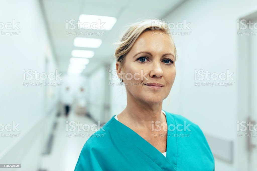 Female healthcare worker standing in hospital corridor stock photo