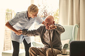istock Female healthcare worker supporting senior man at care home 912073430