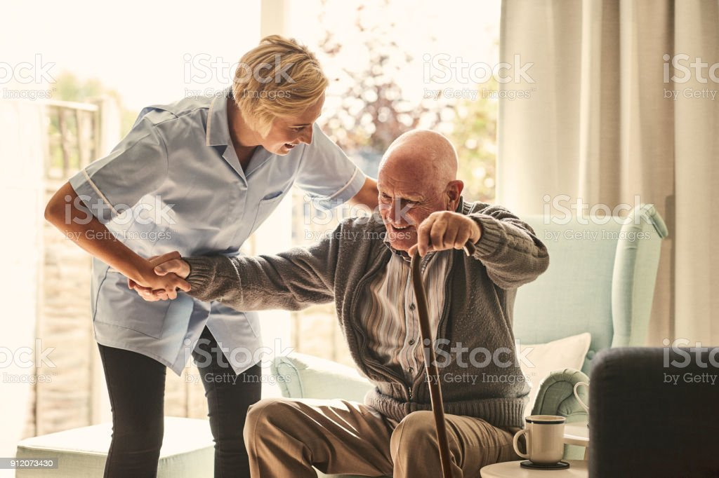 Trabajadora de salud apoyo a hombre mayor en el cuidado del hogar - foto de stock