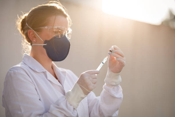 Female healthcare worker withdrawing medication from a vial stock photo