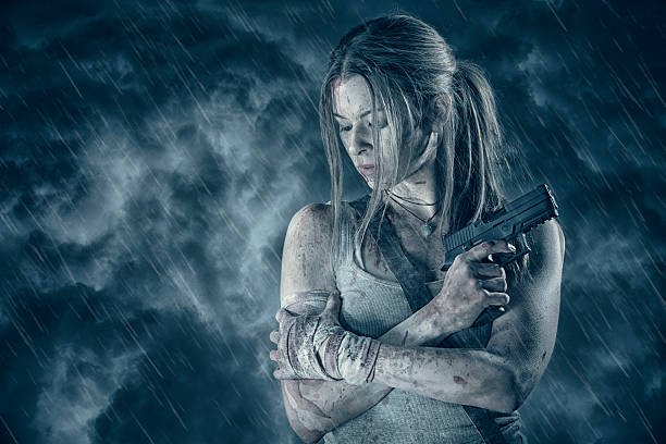 Female heroine holding pistol in rain stock photo