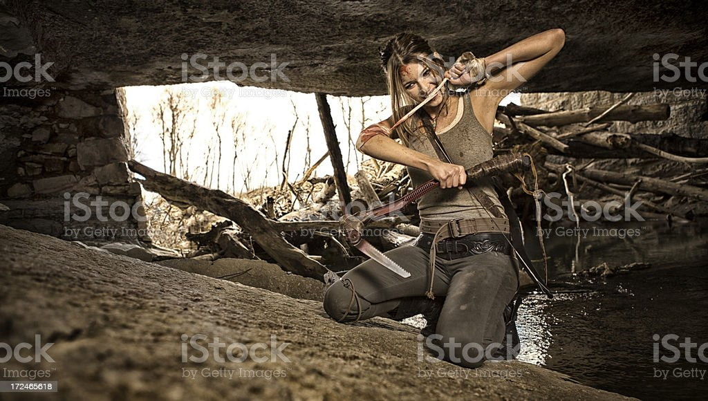 Female heroine with bow and arrow in cave royalty-free stock photo